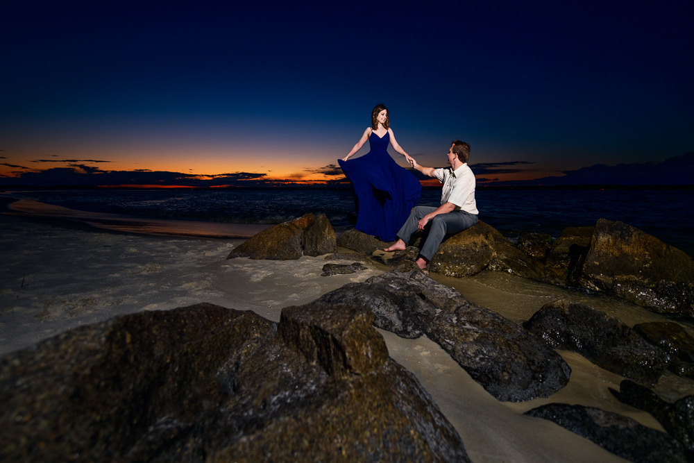 Man sitting on rocks at the beach and Woman spinning her dress at sunset, Fun Engagement Session at Eden Garden and Fort Pickens, Lazzat Photography, engagement photos