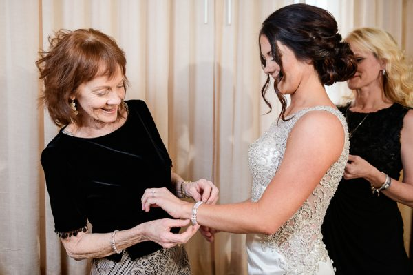 Bride's mom putting on Bride's bracelet, Pensacola Florida, The Pensacola Grand Hotel, Classic Red and White Wedding, Lazzat Photography