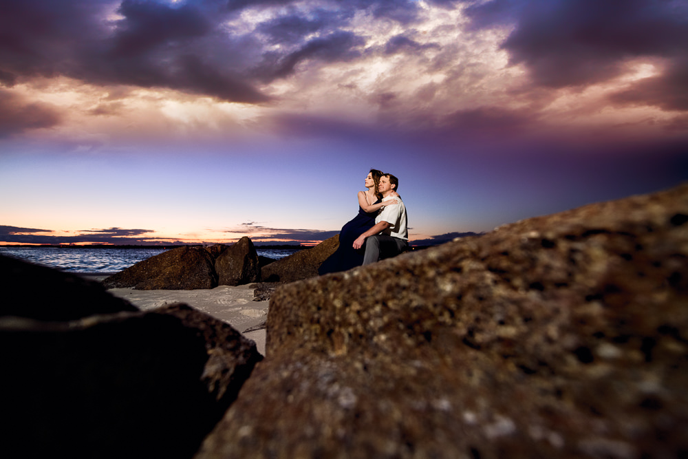 Couple sitting on rocks at the beach at sunset, Fun Engagement Session at Eden Garden and Fort Pickens, Lazzat Photography, engagement photos