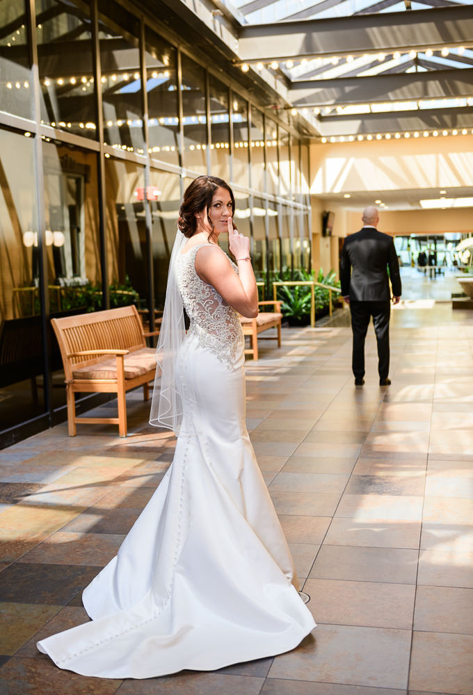 """Bride saying """"shh"""" before first look, Pensacola Florida, The Pensacola Grand Hotel, Classic Red and White Wedding, Lazzat Photography"""