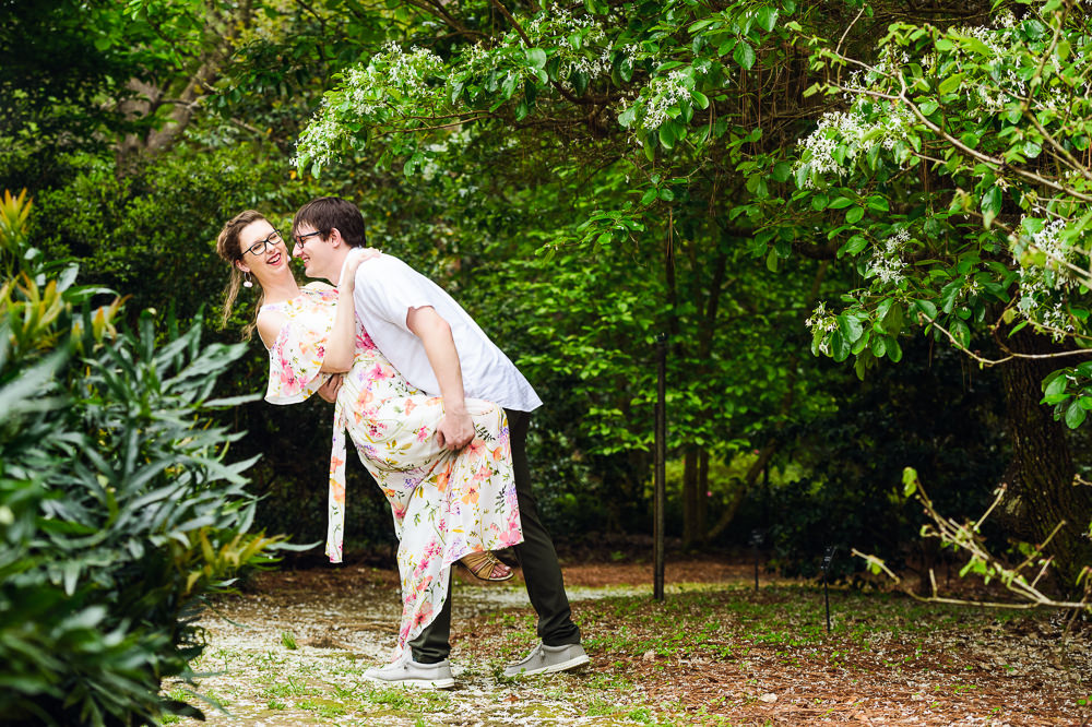 Man dipping his Fiance in a garden, Beautiful Mobile Botanical Gardens Engagement Session, Lazzat Photography
