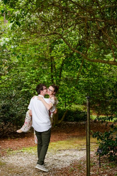 Man carrying his Fiance in a garden, Beautiful Mobile Botanical Gardens Engagement Session, Lazzat Photography