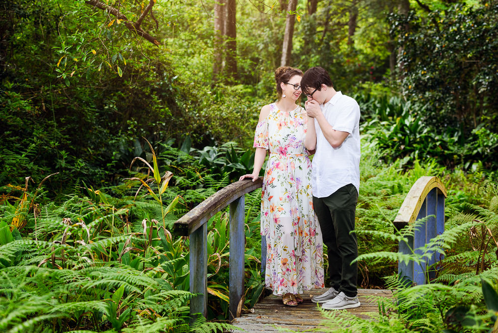 Kissing her hand on a bridge in a garden, Beautiful Mobile Botanical Gardens Engagement Session, Lazzat Photography