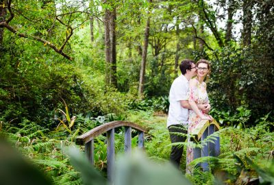 Couple hugging on a bridge in a garden, Beautiful Mobile Botanical Gardens Engagement Session, Lazzat Photography