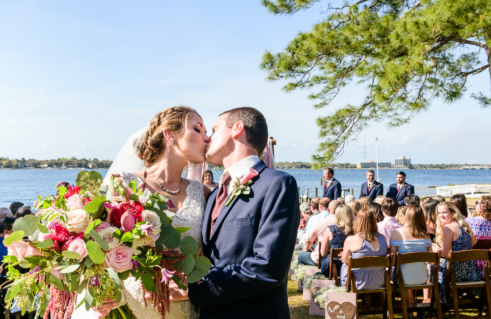 Bride and Groom kissing in the aisle, Rustic Waterfront Wedding, Fort Walton Beach, Fort Walton Yacht Club, Florida Wedding, Lazzat Photography