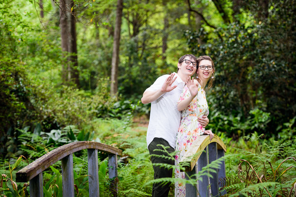 Couple waving on a bridge in a garden, Beautiful Mobile Botanical Gardens Engagement Session, Lazzat Photography