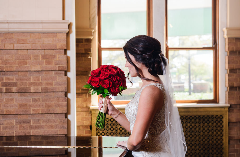 Bride smelling her flowers at The Pensacola Grand Hotel, Classic Red and White Wedding, Lazzat Photography