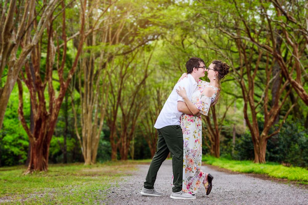 Couple dancing in a lane lined with trees, Beautiful Mobile Botanical Gardens Engagement Session, Lazzat Photography