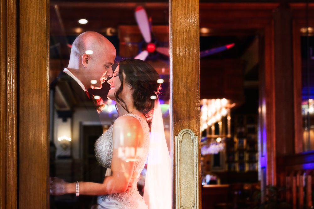 Bride and Groom through a glass door at The Pensacola Grand Hotel, Classic Red and White Wedding, Lazzat Photography