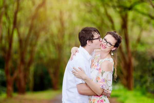 Man kissing her in a lane lined with trees, Beautiful Mobile Botanical Gardens Engagement Session, Lazzat Photography
