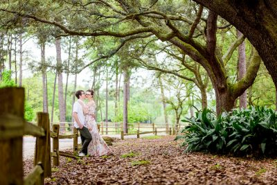 Couple leaning on a wooden fence, Beautiful Mobile Botanical Gardens Engagement Session, Lazzat Photography