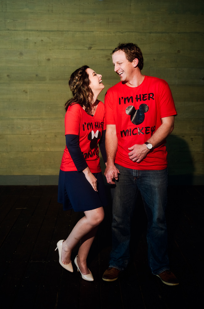 Couple looking at each other and laughing wearing their matching Disney world shirts, Fun Engagement Session at Eden Garden and Fort Pickens, Lazzat Photography, engagement photos