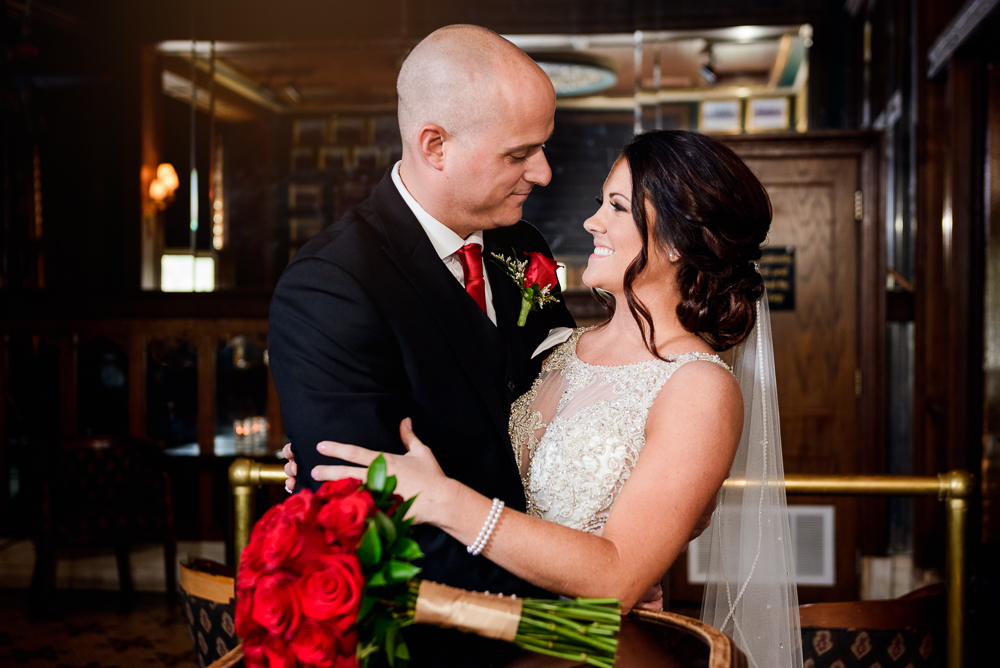 Bride and Groom hugging by the bar at The Pensacola Grand Hotel, Classic Red and White Wedding, Lazzat Photography