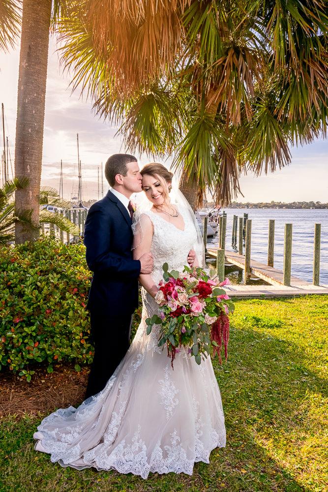 Groom kissing Bride on the forehead under a tree, Fort Walton Beach, Fort Walton Yacht Club, Florida Wedding, Lazzat Photography