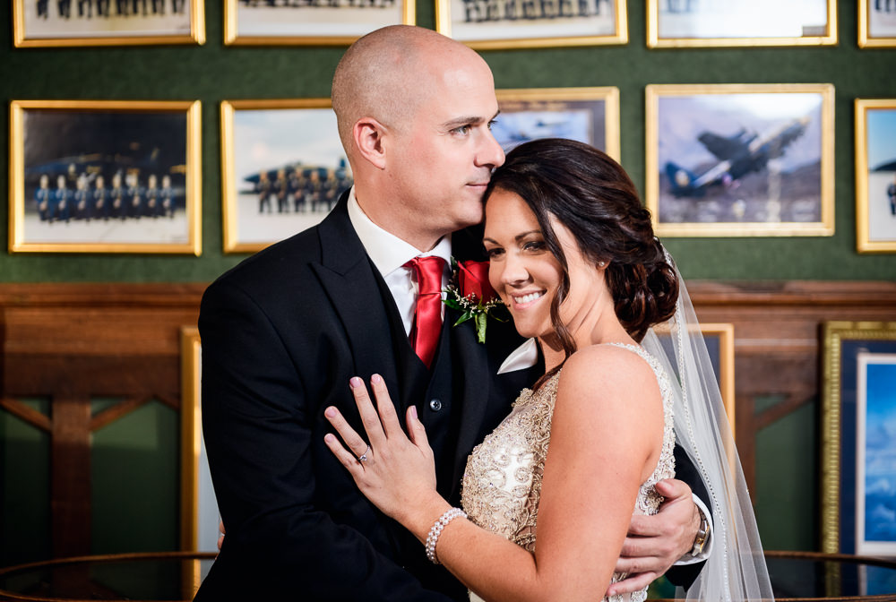 Groom kissing Bride's forehead at the bar at the Pensacola Grand Hotel, Classic Red and White Wedding, Lazzat Photography, wedding photography, wedding photographer