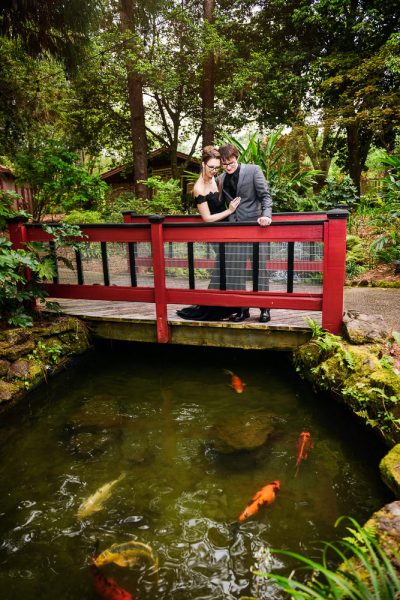 Taylor and Bob standing on a red bridge looking down at koi fish, Beautiful Mobile Botanical Gardens Engagement Session, Lazzat Photography