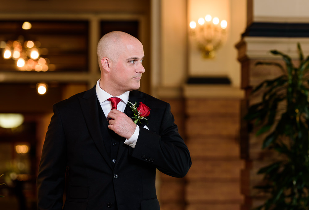 Groom's portrait fixing tie and looking to the side at the Pensacola Grand Hotel, Classic Red and White Wedding, Lazzat Photography, wedding photography, wedding photographer