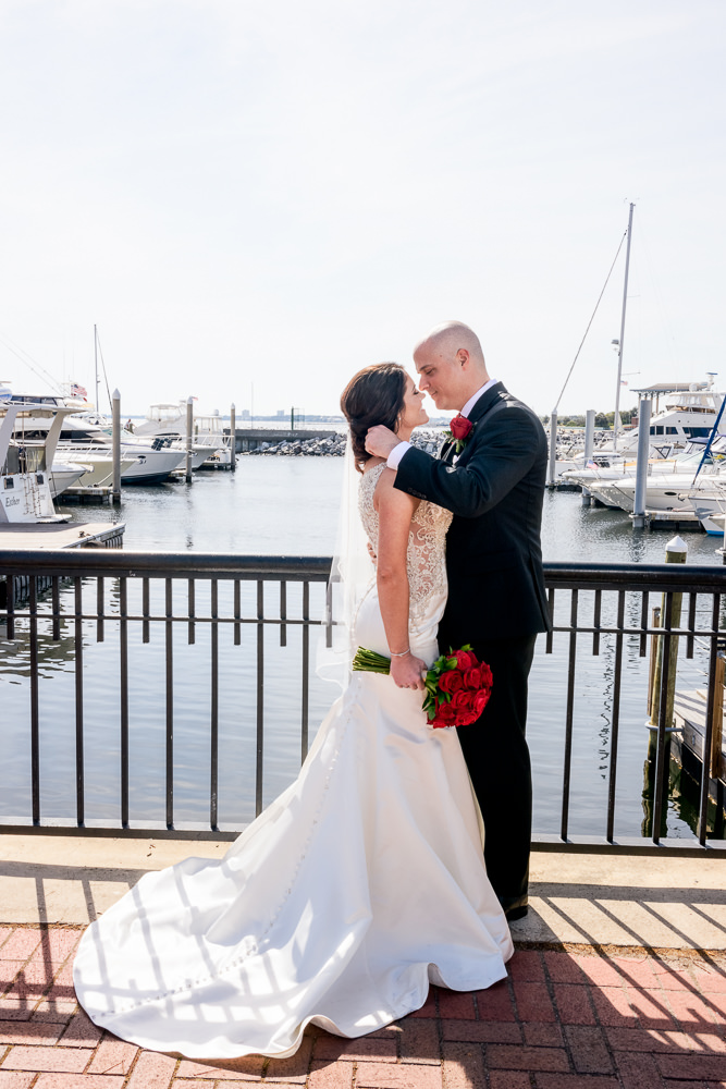 Bride and Groom almost kissing by the water downtown Pensacola Florida, Classic Red and White Wedding, Lazzat Photography, wedding photography, wedding photographer