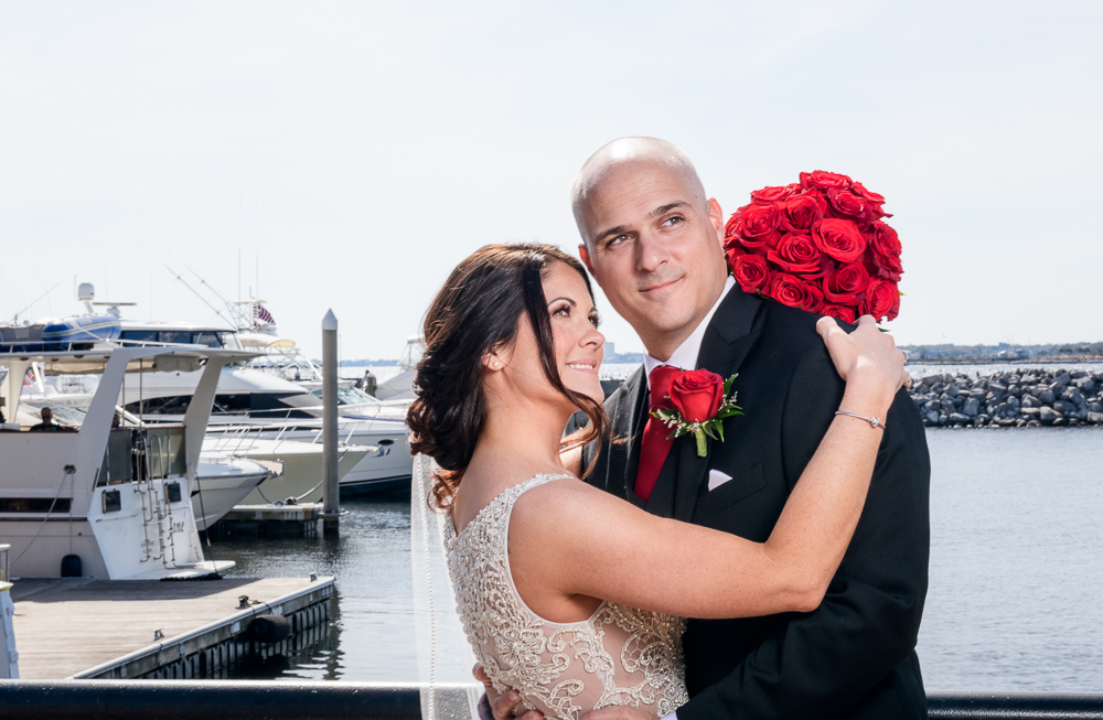 Bride and Groom looking into the distance by the water downtown Pensacola Florida, Classic Red and White Wedding, Lazzat Photography, wedding photography, wedding photographer