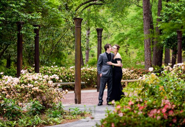 Bob kissing Taylor on the cheek in the circle of columns, Beautiful Mobile Botanical Gardens Engagement Session, Lazzat Photography