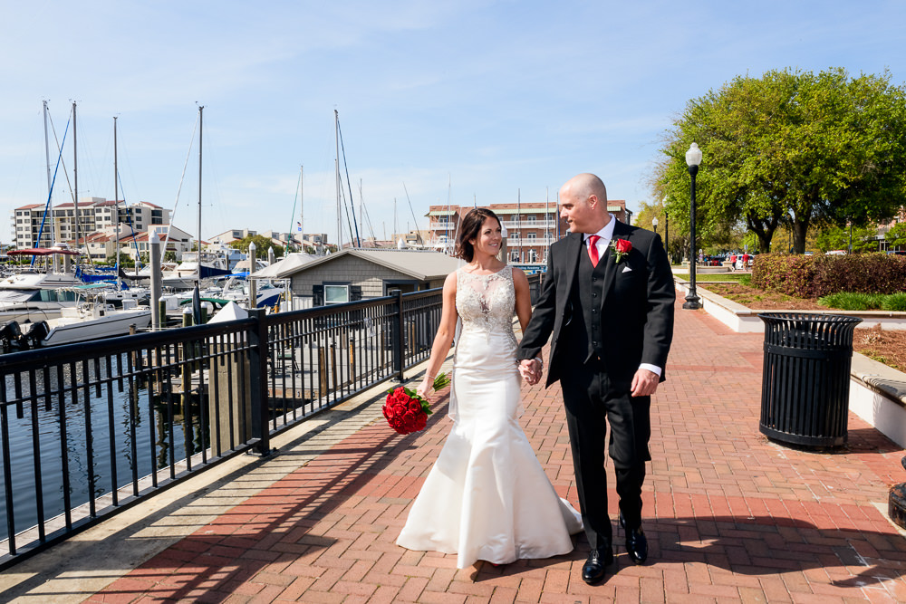 Bride and Groom walking along the water downtown Pensacola Florida, Classic Red and White Wedding, Lazzat Photography, wedding photography, wedding photographer