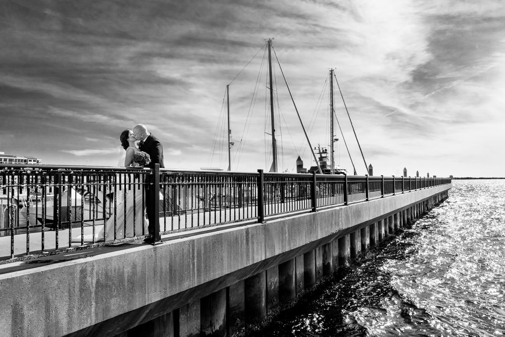Bride and Groom kissing on the pier, black and white, downtown Pensacola Florida, Classic Red and White Wedding, Lazzat Photography, wedding photography, wedding photographer