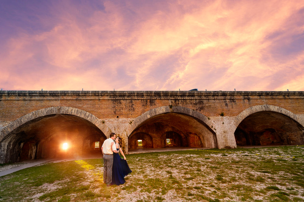 Couple smiling at each other at sunset, Fun Engagement Session at Eden Garden and Fort Pickens, Lazzat Photography, engagement photos