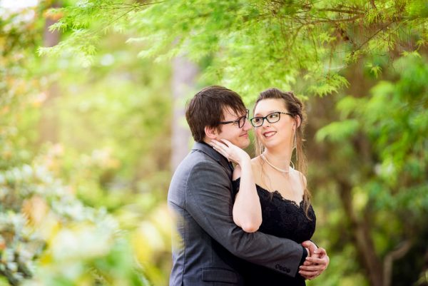Bob hugging Taylor from the back and Taylor touching his cheek, Beautiful Mobile Botanical Gardens Engagement Session, Lazzat Photography
