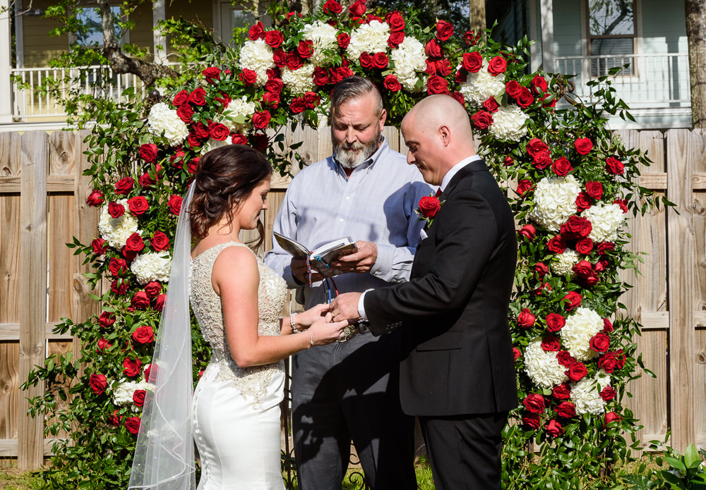 Bride and Groom exchanging rings, outdoor wedding ceremony at the Rails on Wright Street, Classic Red and White Wedding, Lazzat Photography, wedding photography, wedding photographer