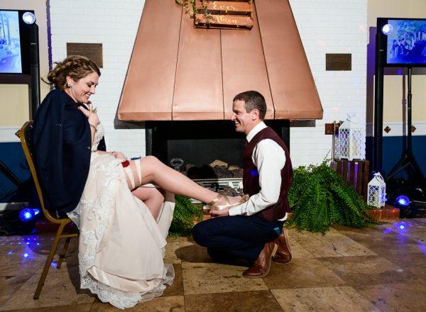 Groom taking off his Bride's garter, Fort Walton Beach, Fort Walton Yacht Club, Florida Wedding, Lazzat Photography