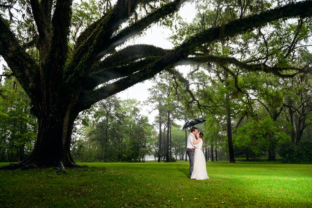 Couple kissing under umbrella in the rain, Fun Engagement Session at Eden Garden and Fort Pickens, Lazzat Photography, engagement photos
