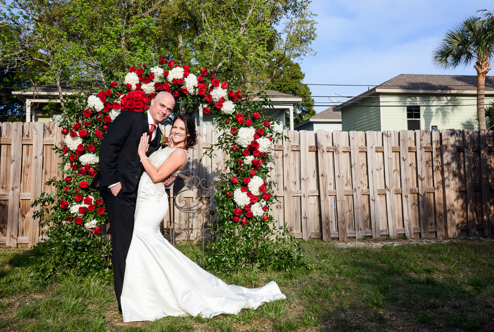 Bride and Groom in front of their red rose wedding arch at the Rails on Wright Street, Classic Red and White Wedding, Lazzat Photography, wedding photography, wedding photographer