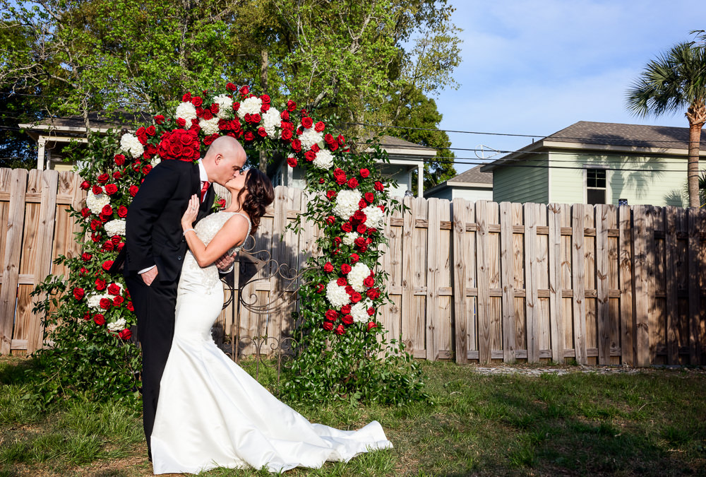 Bride and Groom kissing in front of their red rose wedding arch at the Rails on Wright Street, Classic Red and White Wedding, Lazzat Photography, wedding photography, wedding photographer