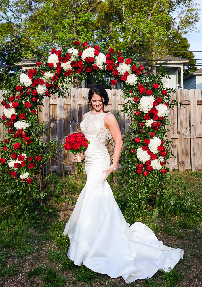 Bride in front of the red rose wedding arch at the Rails on Wright Street, Classic Red and White Wedding, Lazzat Photography, wedding photography, wedding photographer