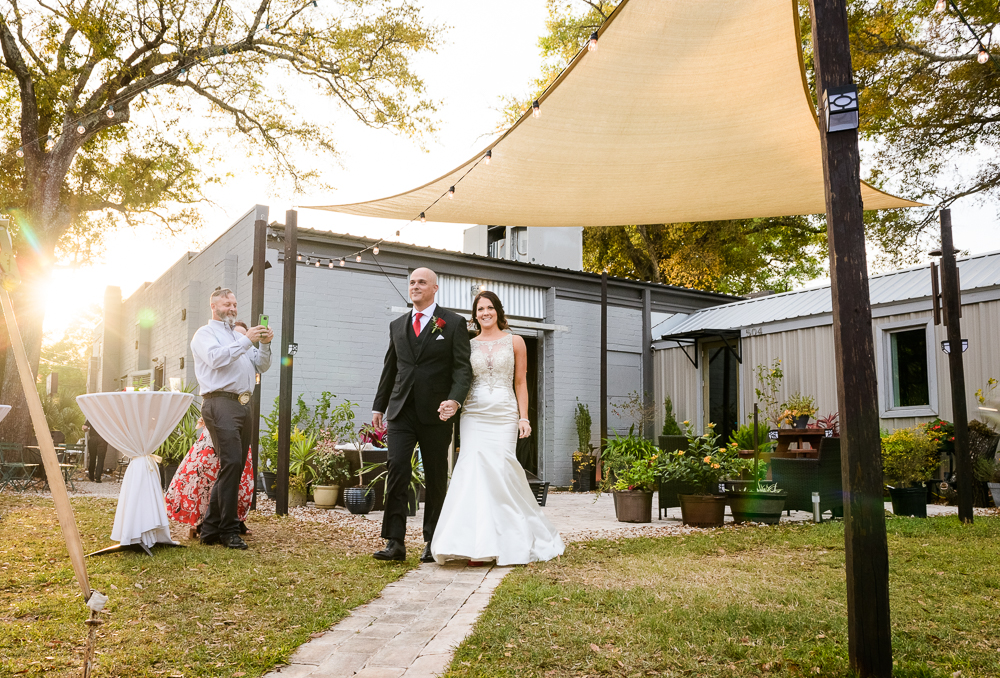Bride and Groom entering their reception at the Rails on Wright Street, Classic Red and White Wedding, Lazzat Photography, wedding photography, wedding photographer