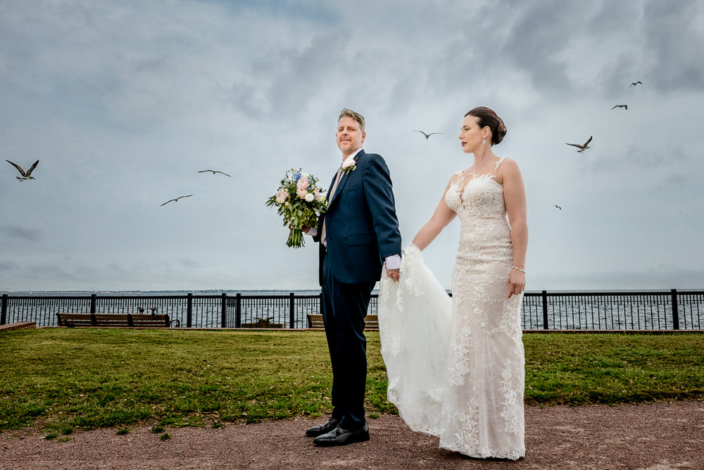 Bride and Groom standing by the water with birds flying, Classic Pensacola Wedding, Lazzat Photography, Florida Wedding Photographer