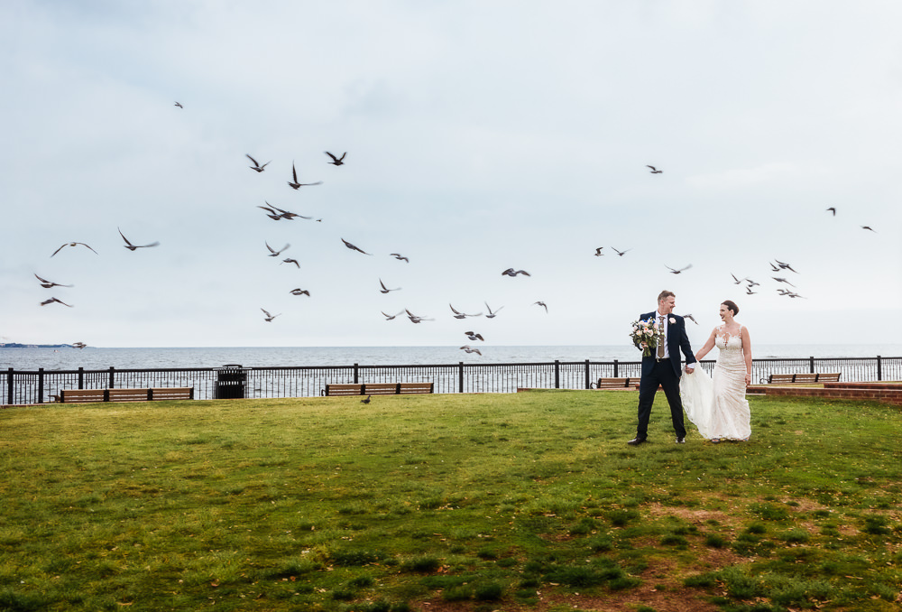 Bride and Groom walking by the water with birds flying, Classic Pensacola Wedding, Lazzat Photography, Florida Wedding Photographer