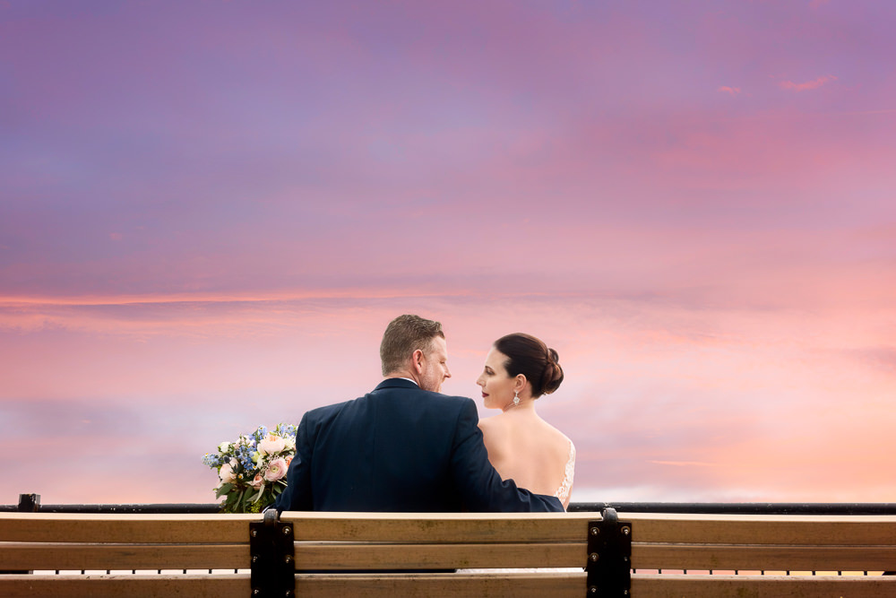 Bride and Groom on a bench at sunset, Classic Pensacola Wedding, Lazzat Photography, Florida Wedding Photographer