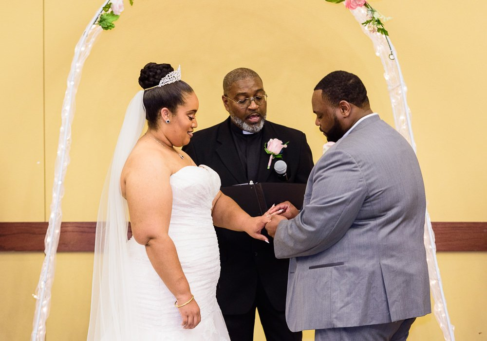 Groom giving his Bride her wedding ring, Blue and Pink Wedding, The Soundside Club, Elegant Ballroom Wedding, Lazzat Photography, Florida Wedding Photography