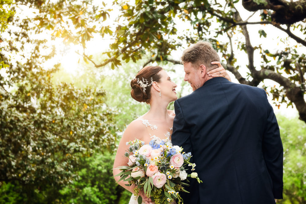 Bride and Groom smiling at each other in a park downtown Pensacola, Classic Pensacola Wedding, Lazzat Photography, Florida Wedding Photographer