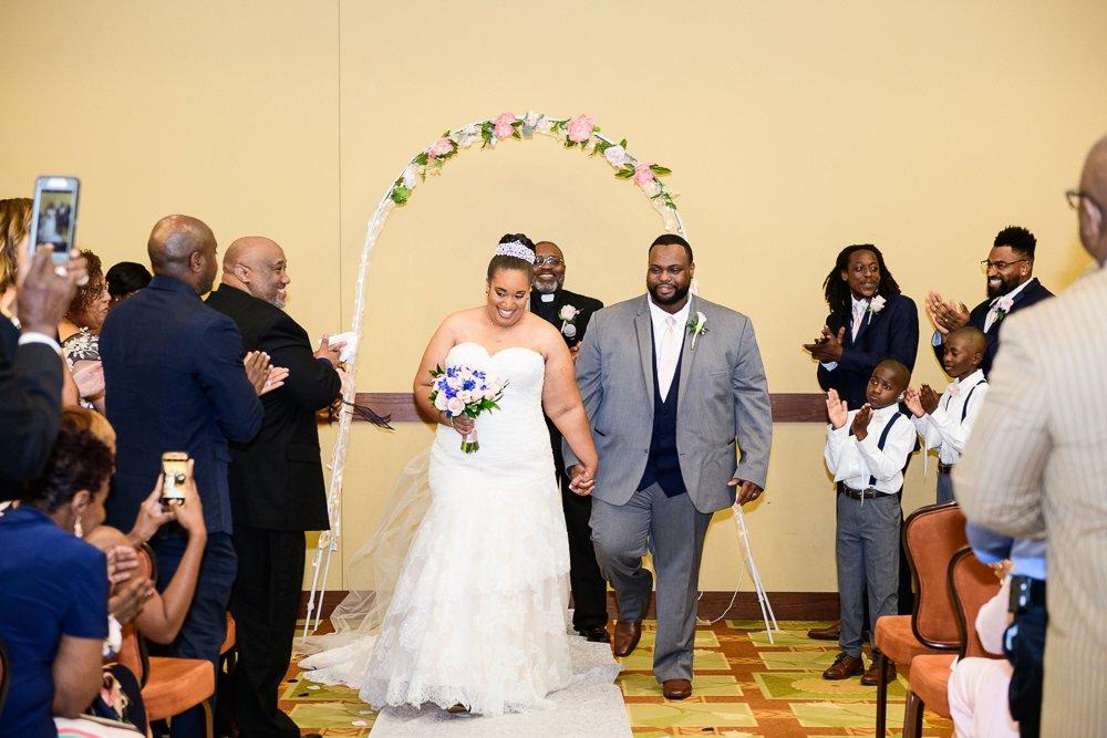 Bride and Groom walking down the aisle, Blue and Pink Wedding, The Soundside Club, Elegant Ballroom Wedding, Lazzat Photography, Florida Wedding Photography