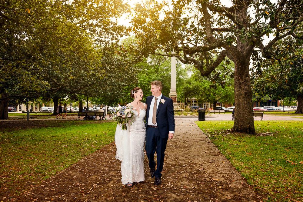 Bride and Groom walking through the park in downtown Pensacola, Classic Pensacola Wedding, Lazzat Photography, Florida Wedding Photographer