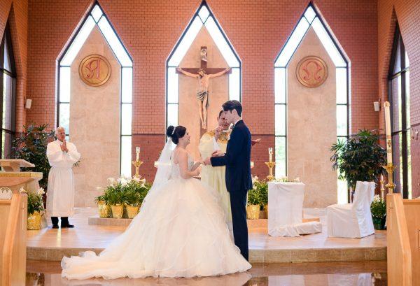 Groom putting Bride's ring on her during their ceremony, Romantic Catholic Wedding, Pensacola Florida Wedding Photographer, Lazzat Photography