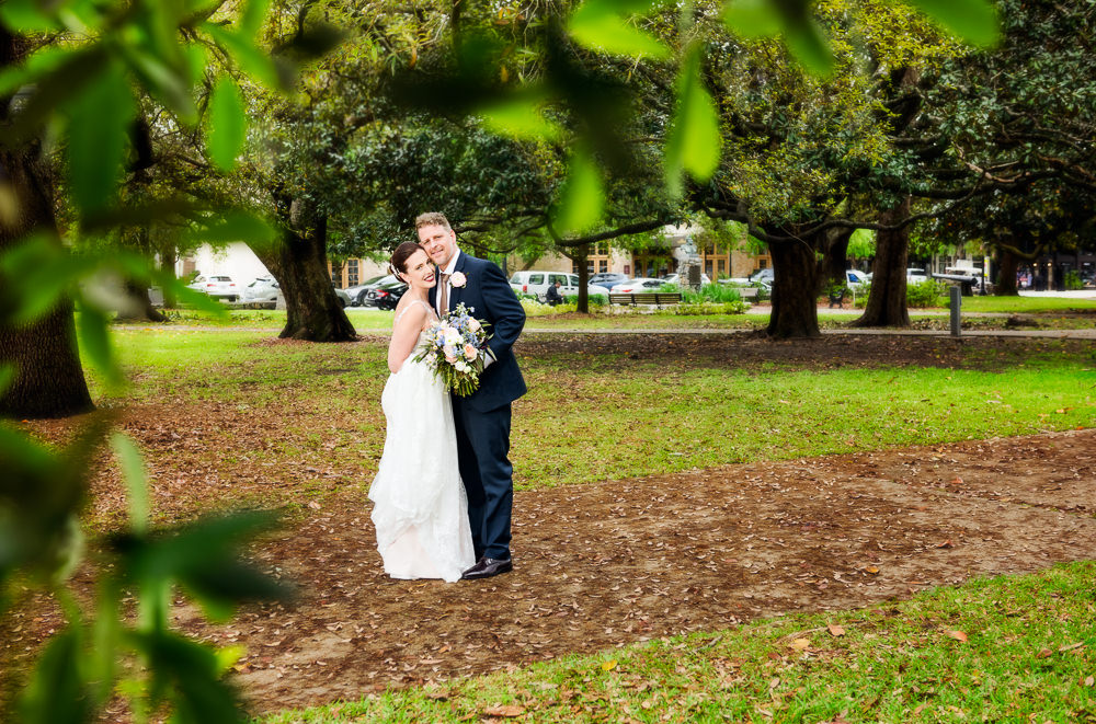 Bride and Groom smiling through the trees in downtown Pensacola, Classic Pensacola Wedding, Lazzat Photography, Florida Wedding Photographer