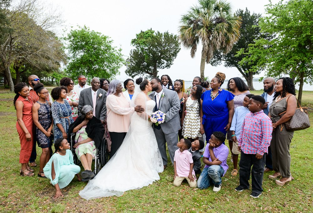 Bride and Groom kissing with Groom's family, Blue and Pink Wedding, The Soundside Club, Elegant Ballroom Wedding, Lazzat Photography, Florida Wedding Photography