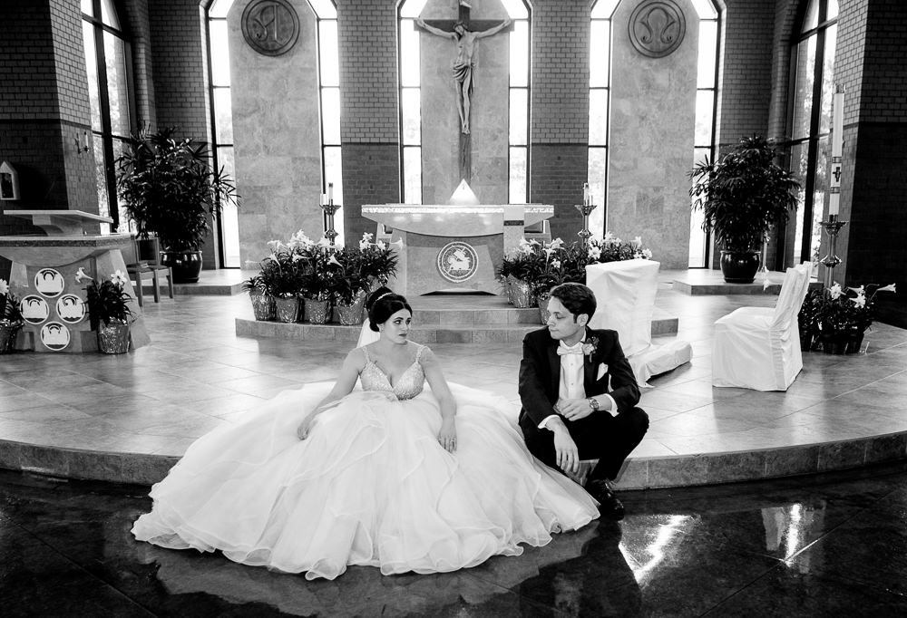 Bride and Groom sitting in their church looking at each other, black and white, Romantic Catholic Wedding, Pensacola Florida Wedding Photographer, Lazzat Photography