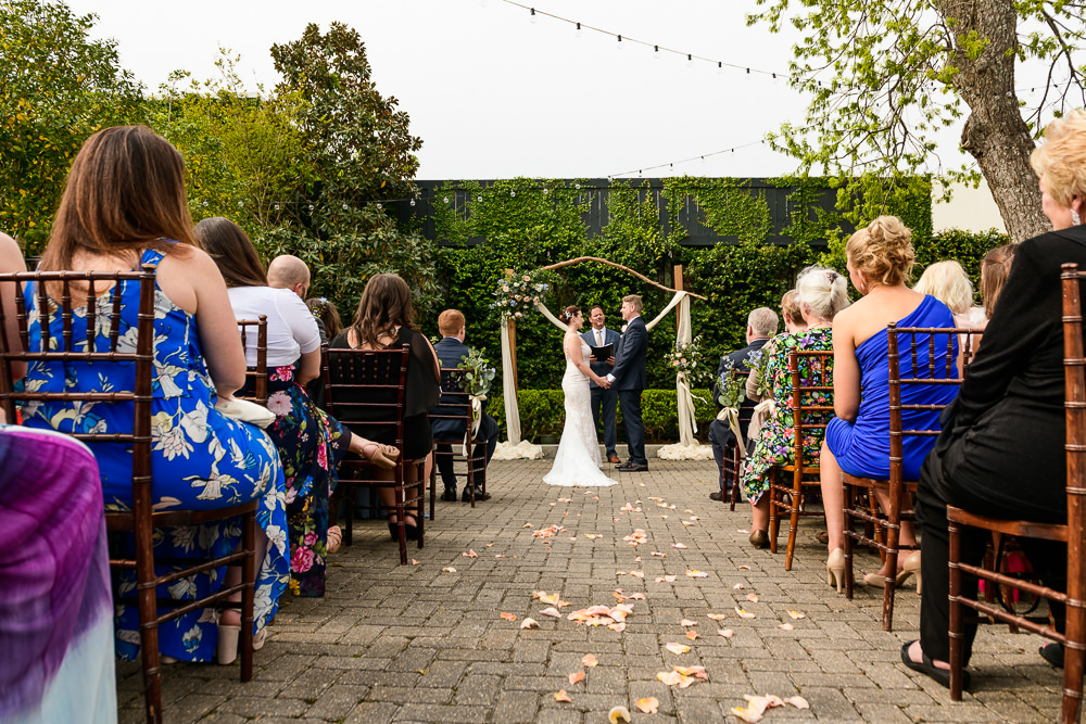 Bride and Groom holding hands at their wedding arch, outdoor wedding ceremony, 5Eleven Palafox, Classic Pensacola Wedding, Lazzat Photography, Florida Wedding Photographer