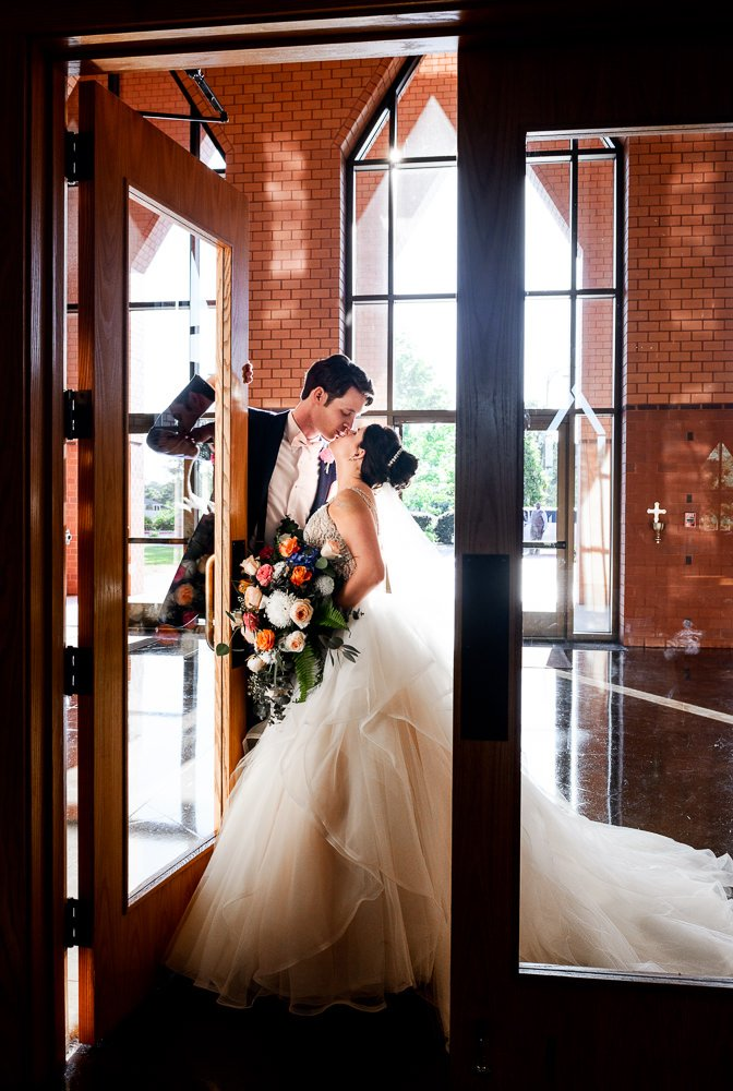 Bride and Groom kissing while leaving the church, Romantic Catholic Wedding, Pensacola Florida Wedding Photographer, Lazzat Photography