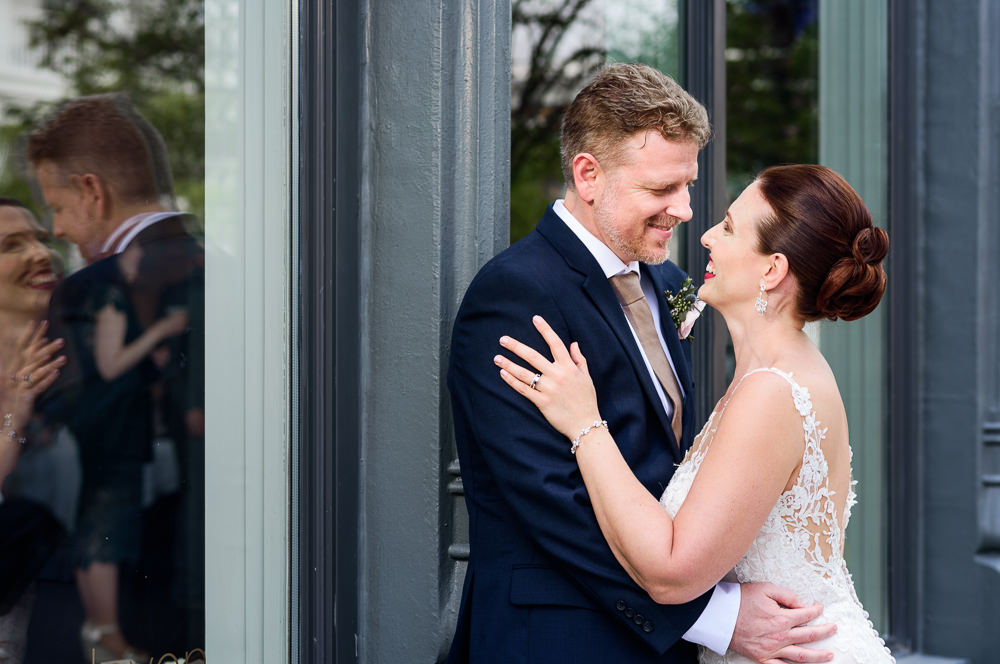 Bride and Groom smiling at each other while standing outside 5Eleven Palafox, Classic Pensacola Wedding, Lazzat Photography, Florida Wedding Photographer