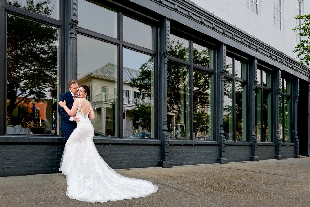 Groom kissing Bride's cheek outside of 5Eleven Palafox, Classic Pensacola Wedding, Lazzat Photography, Florida Wedding Photographer